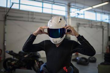Poster Motorise Motorbike driver putiing on his helmet