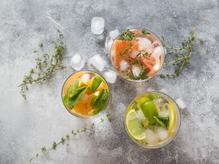 Set summer cold drinks with different citrus in glasses on a gray background. Cocktail with grapefruit, orange, lemon lime, ice and herbs. Refreshing diet drink. Top view. Copy space