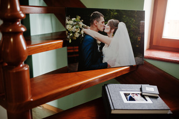 Elegant grey photo book or photo album, flash drive case and a canvas with wedding couple on the stairs.