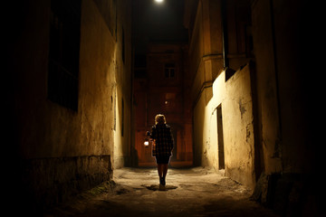 Mysterious blonde woman in elegant retro coat with old oil lantern walking in old French street in Paris, noire atmosphere, investigating crime, detective concept Fotomurales