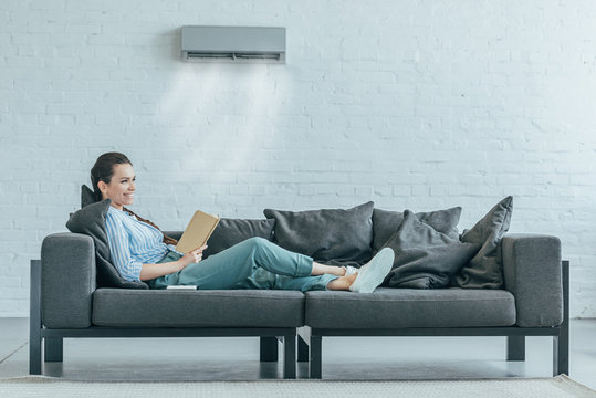 woman reading book on couch, air conditioner blowing on her