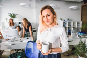 Beautiful girl with a glass of coffee standing in the office