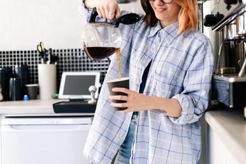 Barista girl pours freshly brewed coffee into a glass