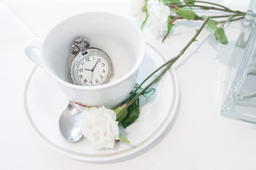 Vintage pocket watch. A closed up of a teacup with antique pocket watch inside. Tea break and tea time concept.