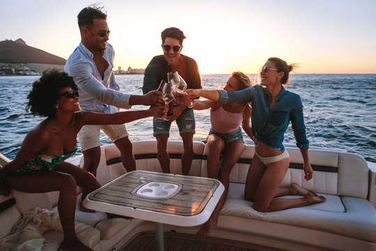 Diverse friends toasting drinks in boat party