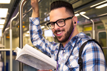 Concept of aspirations, concentration, motivation. Scholar man wearing plaid shirt and glasses studying in the tube.
