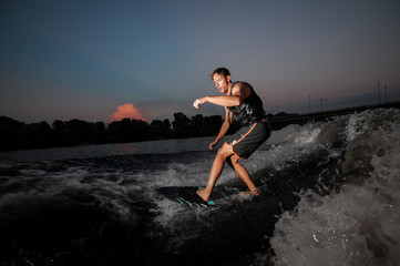 Athletic and young wakesurfer riding on river waves at the sunset