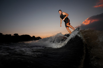 Athletic wakesurfer jumping on board riding down the river waves at the sunset