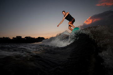 Wakesurfer jumping on board riding down the river waves at the sunset