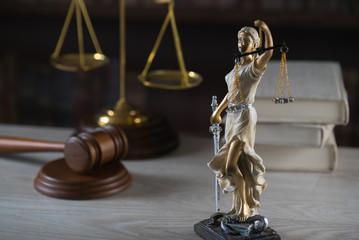 Justice Themis goddess sculpture on dark brown background.