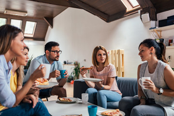 Group of adult friends talking and eating pizza at home.