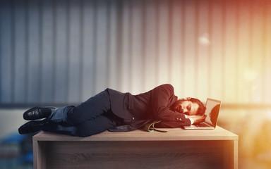 Businessman sleeping over a desk due to overwork