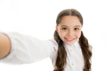 Let me take a selfie. Child girl school uniform clothes holds smartphone takes photo. Child school uniform kid happy face. Girl cute long curly hair holds smartphone taking selfie white background