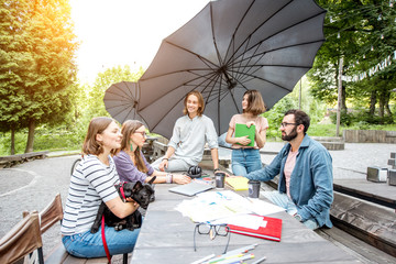 Young friends having fun talking together during a studying outdoors in the park