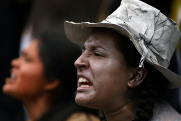 Supporters  of communities affected by toxic metals perform during a protest in front of the Health Ministry in Lima