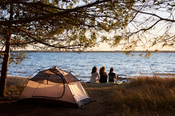 Back view of three tourist girls resting on sea shore in front of tent under tree, enjoying panorama of setting behind horizon sun on clear water background. Tourism, friendship and camping concept.