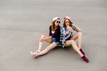 Two young happy girl friends in hipster outfit sitting together on longboard and making selfie on phone
