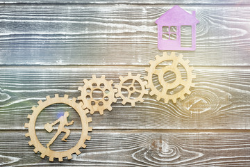 gear, running worker, house on a wooden background. aspiration, real estate. business achievements.