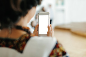 Woman's holding smart phone with blurred background.