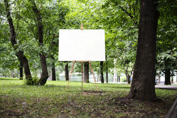 Easel with canvas and green park or forest on the background, 3d rendering.