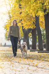 A blonde is walking with a labrador in the park.
