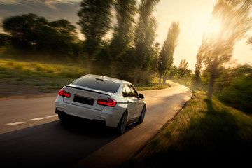 Wall Mural - White car is driving on empty countryside asphalt road at sunset