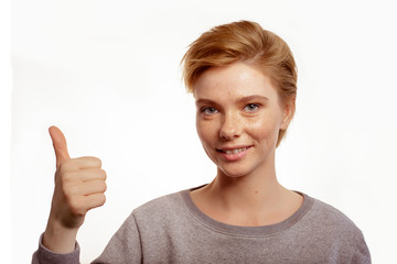 Portrait of a laughing woman showing thumbs up isolated on a white background