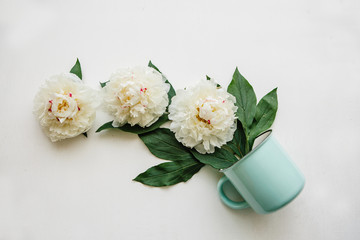A mug of beautiful white flowers is flying out of it. Creative idea