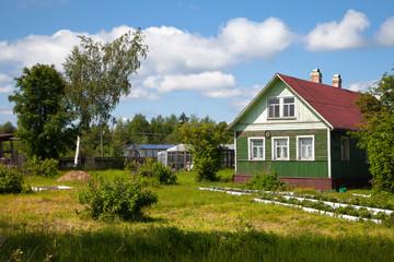 Old wooden house in rural vegetable garden