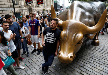 Activist Jeff Jetton, who covered the Wall Street bull with sex toys and posed bare chested and wearing a mask to portray Russia's President Vladimir Putin, poses with the Wall Street Bull in New York