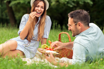 Beautiful happy young couple enjoying their time together, eating fruits and healthy food on picnic in a park. Love and dating, romance, lifestyle concept