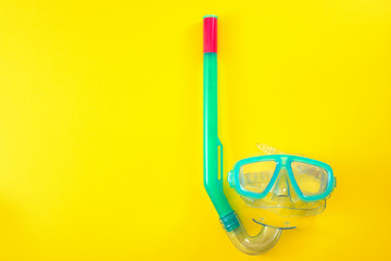 Summer vacation, beach activities and having fun on holiday concept with flat lay image of a snorkeling mask isolated on yellow minimalist background with copy space