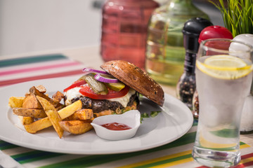 Horizontal color image of Beef Burger with french fries on a white plate on a restaurant table.