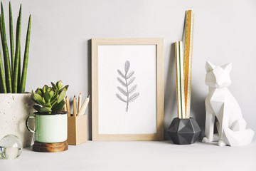 Gray stylish room with wooden mock up poster frame, fox figures, office accessories and design plants. Modern desk in gray interior.