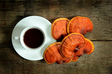 Cup of reishi tea and fresh Lingzhi mushroom on dark wooden floor. (Ganoderma Lucidum). Chinese traditional medicine and nutritive value.