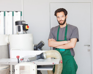 Portrait of a carpenter master with a beard in work clothes in a carpentry workshop near the carpentry equipment