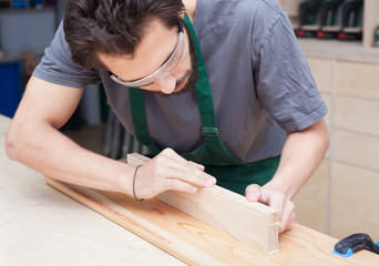Profession, carpentry, woodwork and people concept - carpenter in a gray T-shirt testing wood plank evenness at workshop