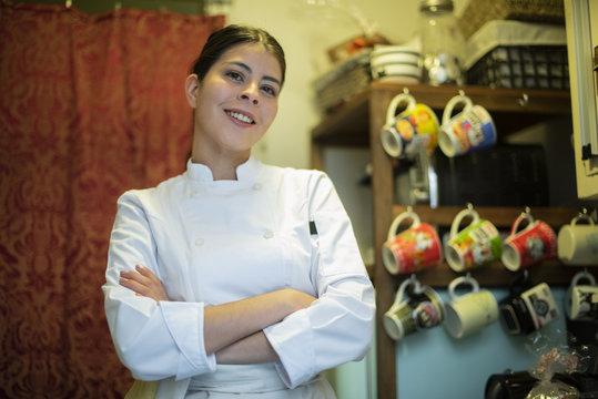 chef latina en cocina con tazas de fondo