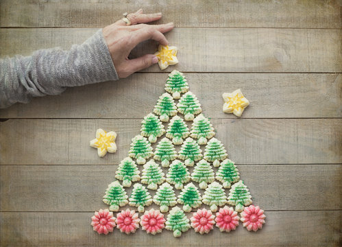 Christmas flat lay photograph of a Christmas tree made out of Spritz cookies with a woman's hand placing a star on top