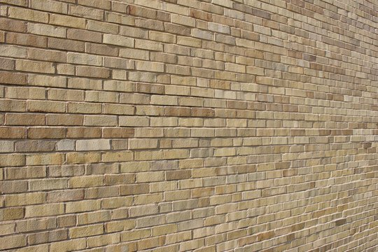 Angle view of an attractive light brown brick wall background with a Flemish stretcher bond pattern