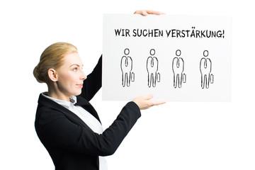 """Geschäftsfrau zeigt Schild mit der Nachricht """"Wir suchen Verstärkung!"""""""
