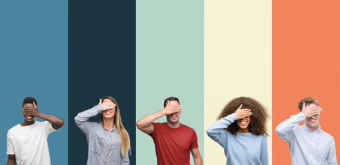 Group of people over vintage colors background smiling and laughing with hand on face covering eyes for surprise. Blind concept.