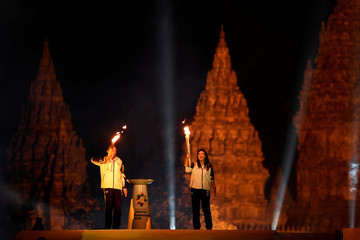 Indonesian badminton legend Susi Susanti (R) holds a flame from India as former tennis player Yustedjo Tarik (L) holds a flame from the Mrapen eternal flame before uniting them in a cauldron during the 2018 Asian Games Torch Relay ceremony at Prambanan Tem