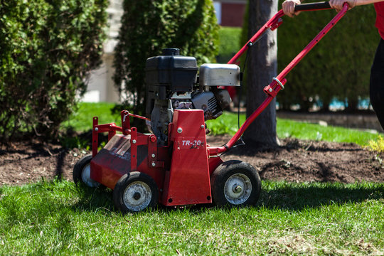 Red lawn aerator pictured on beautiful short green grass