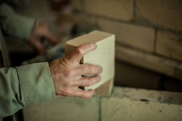 Brickmason's hand holding a brick in front of a brick wall