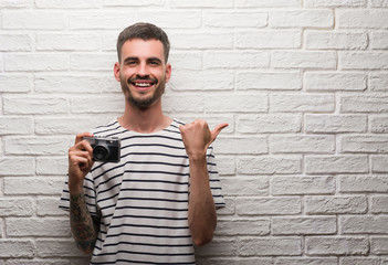 Young man holding vintage camera standing over white brick wall pointing and showing with thumb up to the side with happy face smiling