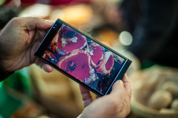 Close up of a phone with a picture of mushrooms in front of a farmer's market stand
