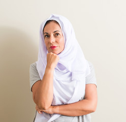 Middle age arabian woman wearing white hijab serious face thinking about question, very confused idea