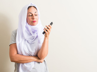 Arabian woman using smartphone serious face thinking about question, very confused idea
