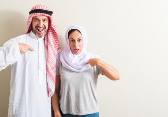 Middle age arabic couple, woman and man with surprise face pointing finger to himself